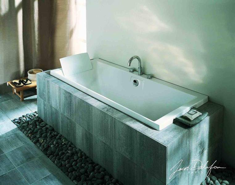 baño con bañera rodeada de piedra de marmol color gris claro con vetas blancas