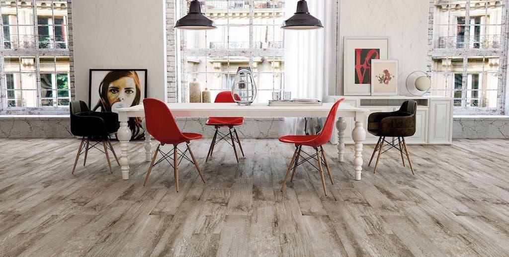 habitacion con suelo de madera de tonos grises claros con una mesa blanca y sillas rojas