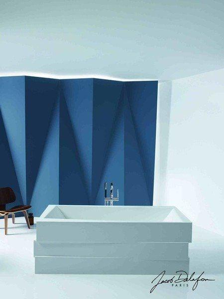 baño con pared de diseño moderno color azul y bañera cuadrada blanca