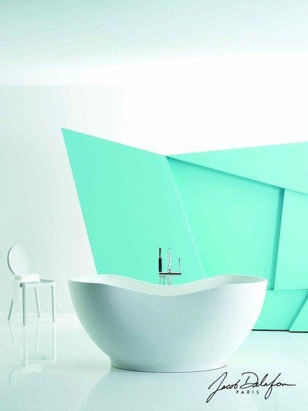 baño con pared moderna de color verde mar con bañera semi redonda en el medio