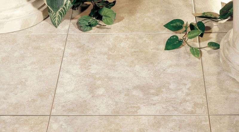 baldosa de suelo imitando piedra de color claro al lado de dos pies de columnas y hojas de plantas