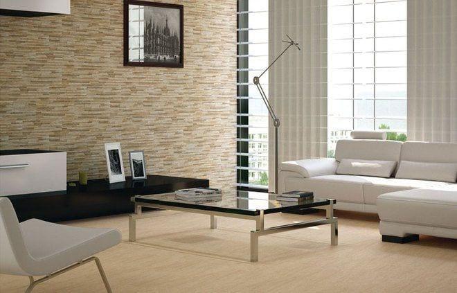 salon con sofas blancos, mesa de centro de cristal y acero, lampara de pie alargadas y parede de piedra
