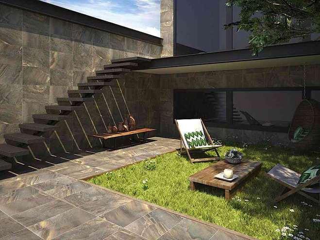 jardin exterior del porche de una casa con escalesras de acceso, dos mesas y una mesa de madera