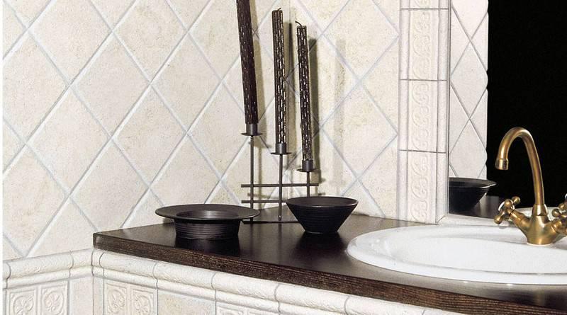 azulejos en pared imitacion piedra en cuarto de baño con lavabo blanco, grifo dorado y encimera de madera oscura