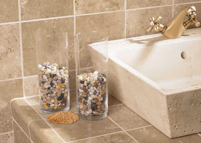 lavabo de marmol travertino con grifo dorado, dos vasos largos llenos de piedras pequeñas