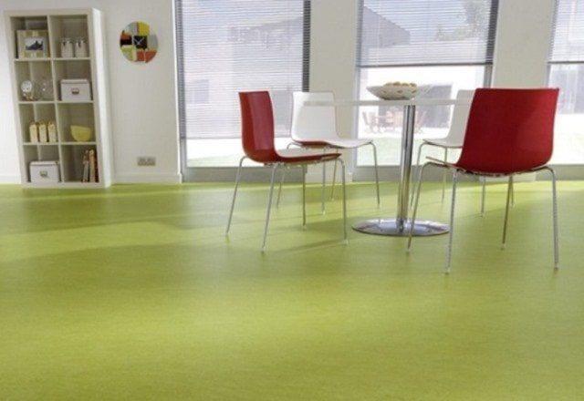 comedor con mesa y cuatro sillas con cristaleras al fondo y estantería blanca. suelo de cocina de color aguacate