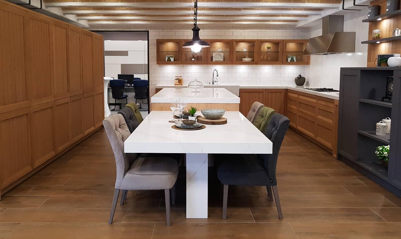 cocina con muebles de madera de pino con mesa de silestone blanca y sillas forradas en terciopelo suave