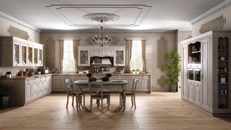amplia cocina con mesa de madera en el centro y sillas, gran lampalara colgada del techo y al fono dos ventanas con cortinas
