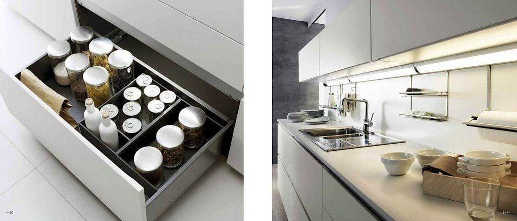 cajón bajo de armario de cocina donde hay latas de comida, al lado cocina blanca con fregadero con grifo de acero