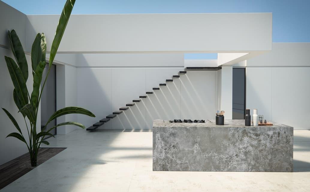 vista del exterior del patio de una casa realizada con material dekton decorada con una platan y unas escaleras al iare al fondo de la imagen