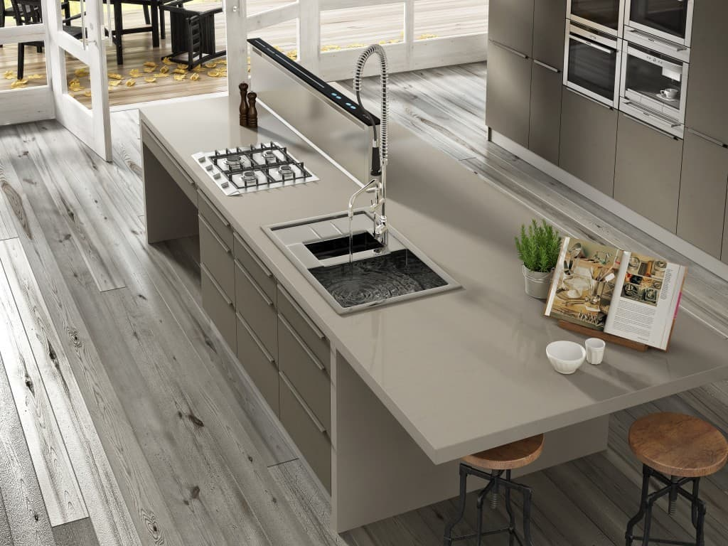vista superior de una cocina donde una gran encimera que hace de isla en el centro de la cocina tiene un fregadero y grifo alargado