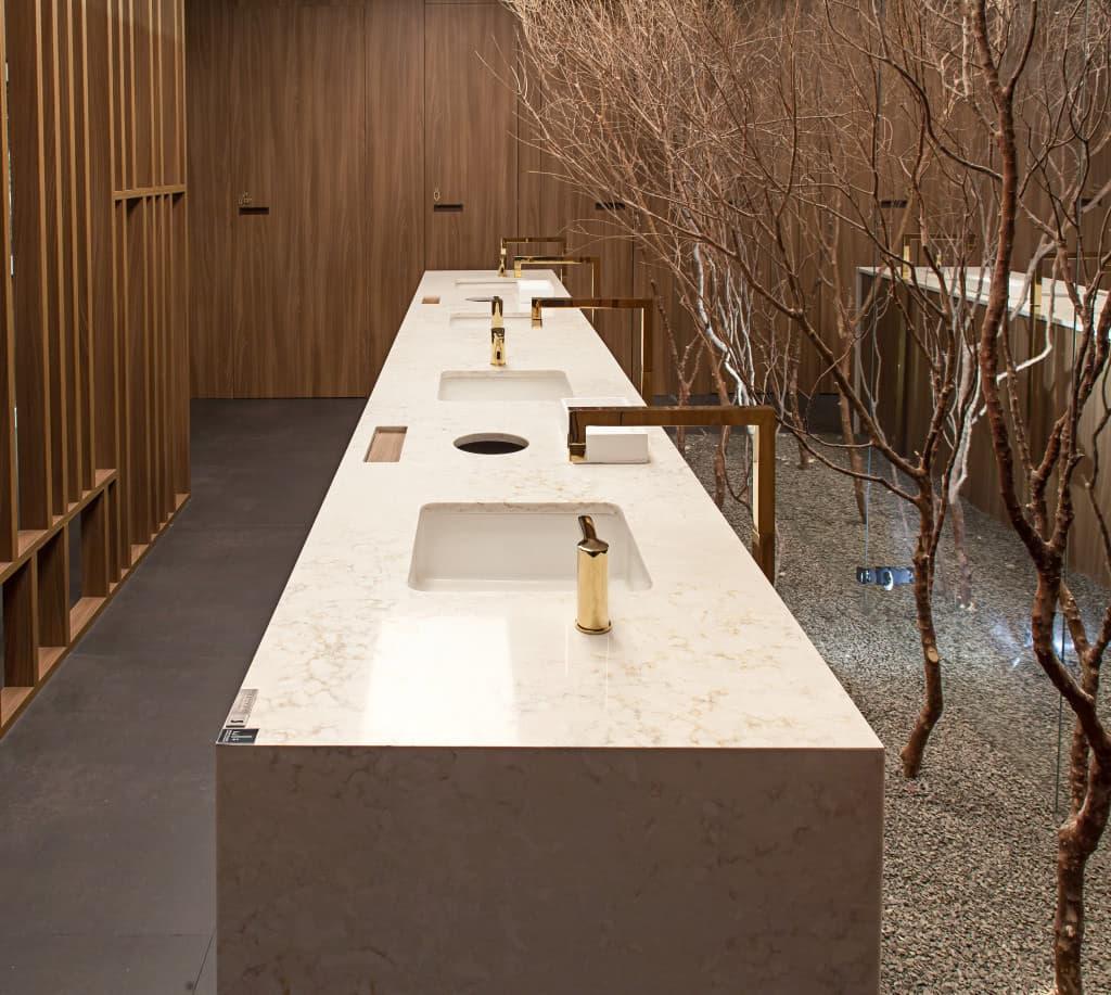 encimera con tres senos de lavabo y tres grifos en una estancia decorada con arboles y puertas de madera