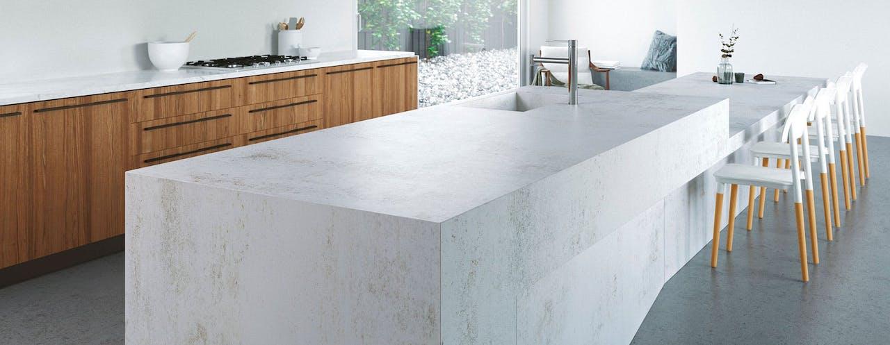 cocina con material dekton en la encimera de color blanco con muebles de madera claros