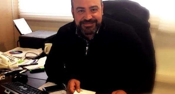 persona en la oficina trabajando con papeles en la mano, un telefono, un teclado y una impresora al fondo