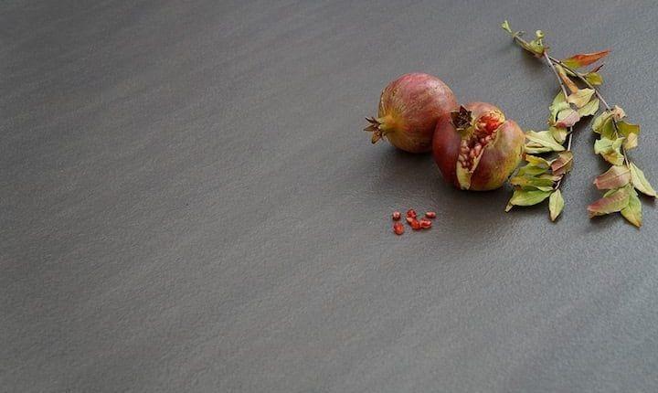 dos piezas de fruta granada sobre encimera de piedra cuarcita gris claro