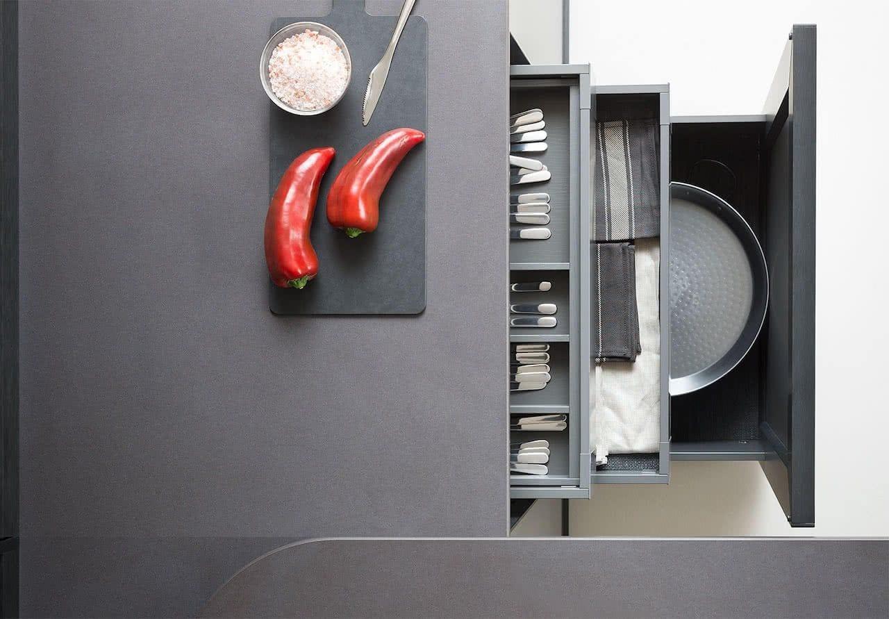 vista superior de encimera cuarcita de cocina con dos pimientos rojos encimas - abajo dos cajones abiertos